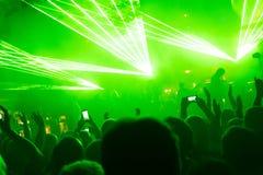摇滚乐音乐会,举手的愉快的人民剪影  免版税库存图片