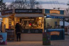 摊位的女推销员与蜂产品在圣诞节市场上 免版税库存照片