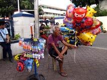 摊贩在公园卖泡影制造商和漫画人物气球 库存照片