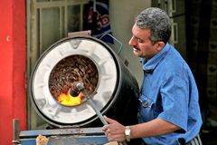 摊贩在旋转筒的烧烤坚果。伊拉克库德斯坦。伊拉克 库存照片