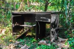 摒弃在不良状态的打破的胶合板书桌 库存照片