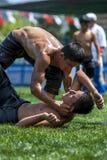 摔跤手帮助他的从草皮的被击败的对手在凯梅尔土耳其石油搏斗的节日在土耳其 库存照片