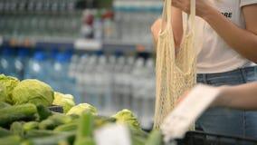 摘素食者和果子在supernarket的俏丽的女孩妇女在滤网有机购物带来,零的废物,友好的eco 股票录像