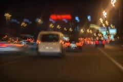 摘要在城市,明亮的刹车灯弄脏了移动的白色汽车并且斋戒驾驶交通在晚上 免版税库存照片