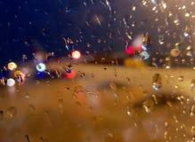 摘要被弄脏有雨珠和bokeh闪烁的湿窗玻璃在阴暗雨天点燃背景 免版税图库摄影