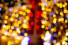 摘要被弄脏红色和金子闪烁的亮光电灯泡点燃背景,圣诞节墙纸装饰迷离  图库摄影