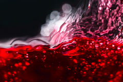 摘要飞溅红葡萄酒在黑背景 免版税库存照片