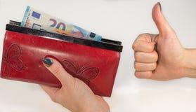 摘要-拿着有金钱的妇女手红色钱包 免版税库存图片