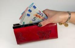 摘要-拿着有金钱的妇女手红色钱包 免版税图库摄影