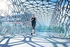 摘要-跑在一座现代桥梁的美丽的妇女 免版税图库摄影