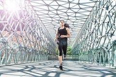 摘要-跑在一座现代金属桥梁的美丽的妇女 库存图片
