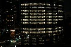 摩天大楼发光的窗口晚上-现代办公室和塔看法  免版税库存图片