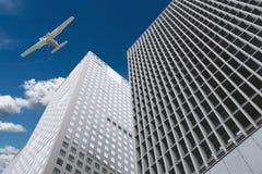 摩天大楼和飞机在天空 免版税库存图片