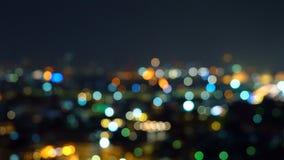 摩天大楼大厦Bokeh在有光的城市,在夜间的模糊的照片 都市风景背景 免版税图库摄影