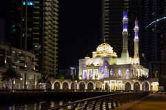 摩天大楼背景的清真寺在晚上 都市风景迪拜海滨广场全景场面日落 库存图片