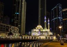 摩天大楼背景的清真寺在晚上 都市风景迪拜海滨广场全景场面日落 免版税图库摄影