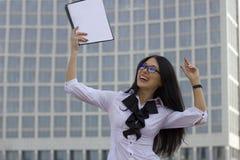 摩天大楼背景的年轻女商人  喜悦和satisf 免版税库存照片