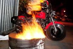 摩托车停放在与火的桶之间 图库摄影