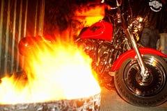 摩托车停放在与火的桶之间 免版税库存照片