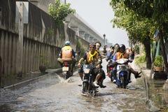 摩托车出租汽车和志愿者运载的人们通过的洪水在路去猛击pai寺庙 免版税库存照片