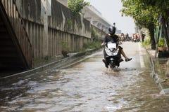 摩托车出租汽车和志愿者运载的人们通过的洪水在路去猛击pai寺庙 免版税库存图片