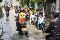 摩托车出租汽车和志愿者运载的人们通过的洪水在路去猛击pai寺庙 库存照片