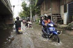 摩托车出租汽车和志愿者运载的人们通过的洪水在路去猛击pai寺庙 免版税图库摄影
