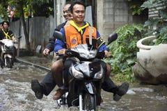 摩托车出租汽车和志愿者运载的人们通过的洪水在路去猛击pai寺庙 库存图片