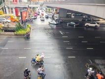 摩托车和汽车是加速,当绿色交通标志出现于四个连接点于Saladaeng附近的Silom和Lumpini 库存图片