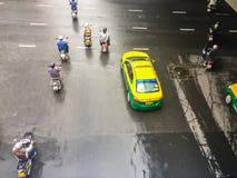 摩托车和汽车是加速,当绿色交通标志出现于四个连接点于Saladaeng附近的Silom和Lumpini 免版税库存照片