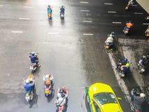 摩托车和汽车是加速,当绿色交通标志出现于四个连接点于Saladaeng附近的Silom和Lumpini 免版税库存图片