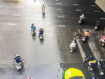 摩托车和汽车是加速,当绿色交通标志出现于四个连接点于Saladaeng附近的Silom和Lumpini 库存照片