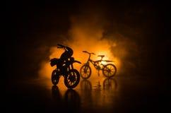 摩托车和自行车剪影在黑暗的多云被定调子的背景 一辆摩托车和自行车的剪影从一张侧视图 Se 免版税库存照片