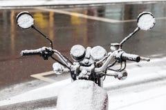 摩托车在用雪盖的街道上停放了 免版税库存照片