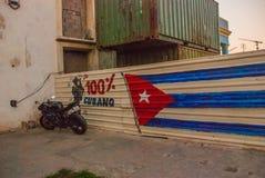 摩托车在篱芭附近停放,图画被做:古巴,在篱芭的街道画的旗子有题字的 库存图片