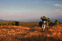 摩托车带着站立在一个宽橙色日落黎明山草甸高原的手提箱的enduro旅客 免版税库存图片