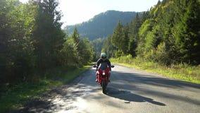摩托车的一个人 年轻英俊的人在山路骑摩托车 股票录像