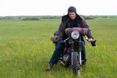 摩托车的一个岗位启示人在草甸 库存照片