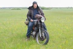 摩托车的一个岗位启示人在草甸 免版税库存图片
