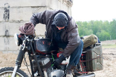 摩托车的一个岗位启示人在被毁坏的大厦附近 免版税库存照片