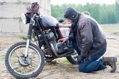 摩托车的一个岗位启示人在被毁坏的大厦附近 库存图片