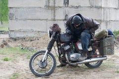 摩托车的一个岗位启示人在被毁坏的大厦附近 免版税库存图片