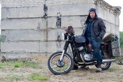 摩托车的一个岗位启示人在被毁坏的大厦附近 图库摄影