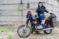 摩托车的一名岗位启示妇女在被毁坏的大厦附近 免版税库存照片