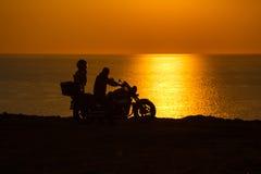 摩托车的两个人在黑海的日落 库存照片