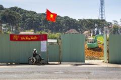 摩托车的人在有挖掘机的建造场所前面和2012年2月10日的越南旗子在大叻,越南 免版税图库摄影