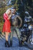 摩托车的人有红色礼服的一个性感的少妇的路 免版税图库摄影