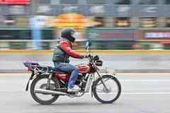 摩托车的人通过商店,广州,中国 免版税库存图片