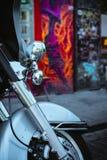 摩托车的前轮和有街道画的一盏前灯围住背景 库存图片