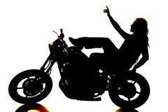 摩托车的指向剪影的妇女  库存图片